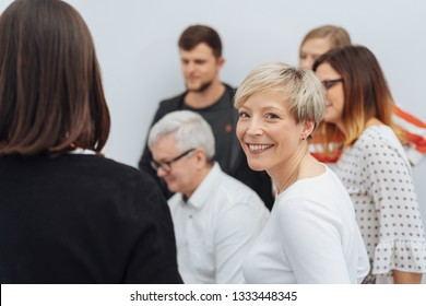 Smiling businesswoman in a meeting with diverse colleagues turning to grin happily at the camera