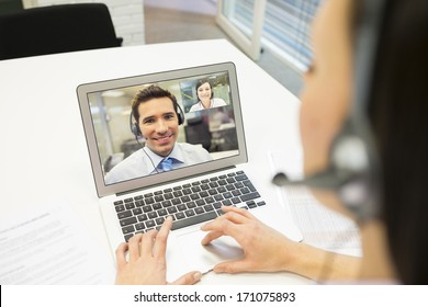 Smiling Businesswoman in the office on video conference, headset, Skype
