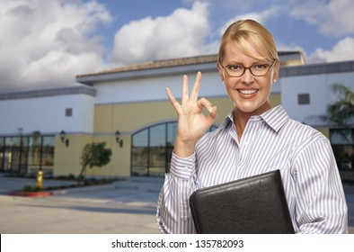 Smiling Businesswoman with Okay Sign In Front of Vacant Office Building.
