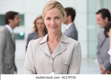 Smiling businesswoman outside with her team
