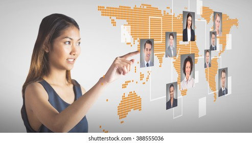 Smiling businesswoman pointing against grey vignette