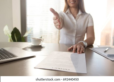 Smiling businesswoman proposes partnership, gives hand at camera for handshake, offers to sign contract, makes business proposition, good deal proposal, ready to conclude agreement at desk, close up