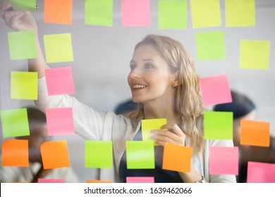 Smiling businesswoman removing sticky papers with finished tasks from scrum board, colorful post it notes, successful happy leader coach planning corporate project at glass wall, adding ideas