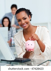 Smiling businesswoman saving money in a piggy-bank at her desk