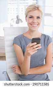 Smiling businesswoman sending a text at her desk in her office