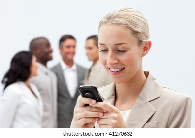Smiling businesswoman sending a text with a mobile phone in workplace with her team in the background