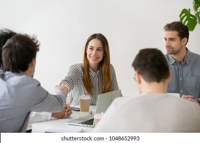 Smiling businesswoman shaking hand of male partner at negotiations, friendly woman handshaking man greeting new team member at group meeting, respect or first impression, making business deal concept