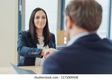 Smiling businesswoman shaking hands with a businessman sitting opposite her at a desk as she concludes an agreement in an over the shoulder view