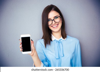 Smiling businesswoman showing blank smartphone screen over gray background. Wearing in blue shirt and glasses. Looking at camera.