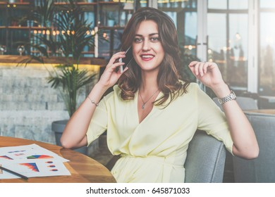 Smiling businesswoman sitting alone at table in cafe and calling by cell phone. Telephone negotiations with a business partner. On table paper graphs, charts, diagrams. Instagram filter. Lifestyle.