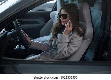 Smiling businesswoman sitting in the car and holding tablet pc. Technology and business concept. Horizontal shot, Outdoors