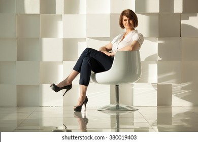 Smiling businesswoman sitting in chair with crossed legs against of white wall made of cubes.