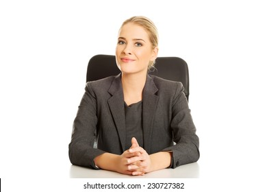 Smiling businesswoman sitting at the desk.