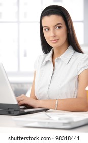 Smiling businesswoman sitting at desk working with laptop computer.
