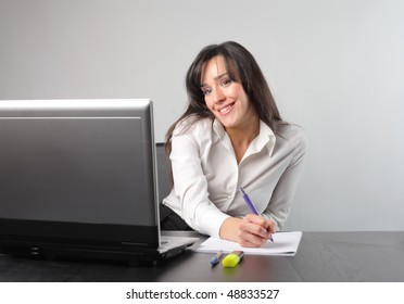 Smiling businesswoman sitting in front of a laptop