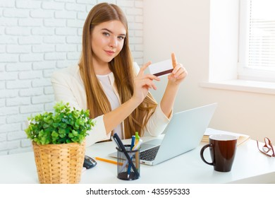 Smiling businesswoman sitting at her workplace in office and talking on the phone