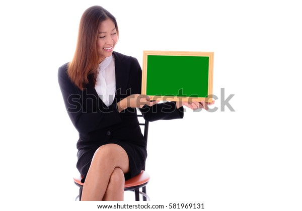 Smiling  businesswoman sitting and holding  green banner on white background.