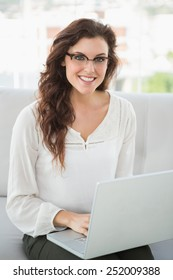 Smiling businesswoman sitting on couch using laptop in the office