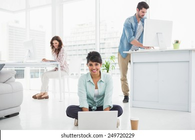 Smiling businesswoman sitting on the floor using laptop with colleagues behind her