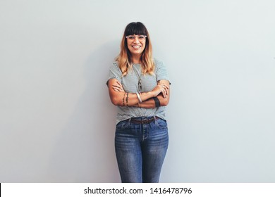 Smiling businesswoman standing against the wall with arms crossed. Cheerful woman in jeans trousers and tshirt standing with folded hands.