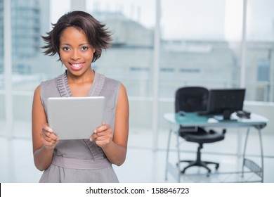 Smiling businesswoman standing in her office and holding tablet while looking at camera