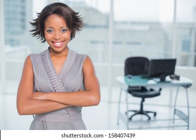 Smiling businesswoman standing in office and crossing her arms while looking at camera