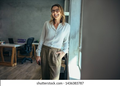 Smiling businesswoman standing in office. Online business owner in casuals standing by window in office looking away and smiling.