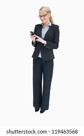 Smiling businesswoman standing and using mobile phone