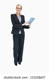 Smiling businesswoman standing while holding and using tablet pc
