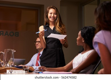 Smiling businesswoman stands presenting to team at meeting