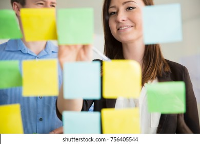 Smiling Businesswoman Sticking Notes On Glass By Colleague