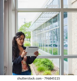 Smiling businesswoman with tablet inside college