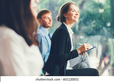 Smiling Businesswoman Taking Notes at Conference