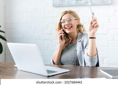 smiling businesswoman talking by smartphone and using laptop in office