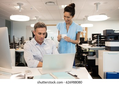 Smiling businesswoman talking with male colleague sitting at desk in office