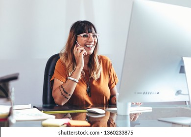 Smiling businesswoman talking on mobile phone while looking at a computer. Cheerful entrepreneur working in office sitting at her desk.