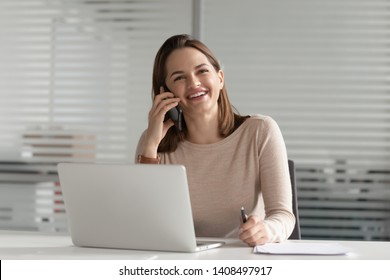 Smiling businesswoman talking on phone make business call at work, happy young entrepreneur female secretary consulting client chatting with friend laughing having mobile conversation in office