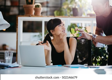 Smiling businesswoman talking with partner while sitting at her desk. Professional employees discussing ideas of project on laptop.
