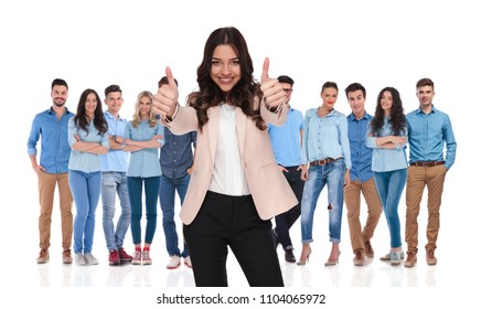 smiling businesswoman team leader making ok sign while standing in front of her young casual group