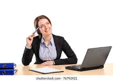 A smiling businesswoman in thought posing in her office