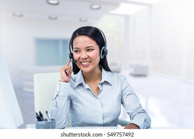 Smiling businesswoman using headset against view of modern interior