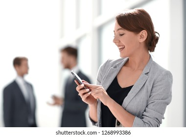 smiling businesswoman using her smartphone