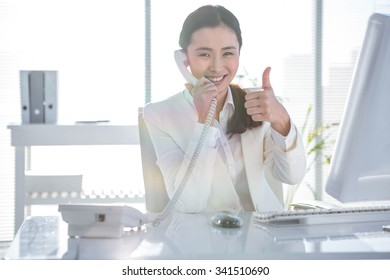 Smiling businesswoman using her telephone at the desk in work