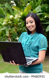smiling businesswoman using laptop in nature