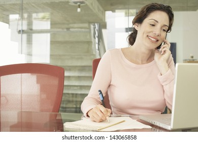 Smiling businesswoman using mobile phone while writing on notepad with laptop on table