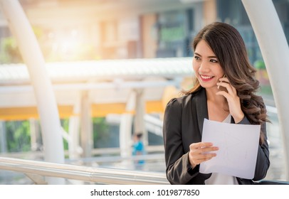Smiling businesswoman using smart phone and holding a paper document