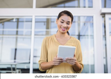 Smiling businesswoman using tablet while standing in office