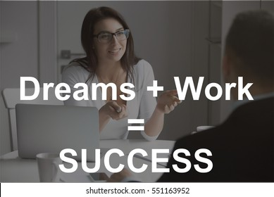 """Smiling businesswoman wearing glasses talking to a male candidate at the desk, interviewing a job applicant. Photo with motivational text """"Dreams + work = Success"""". Business concept photo"""