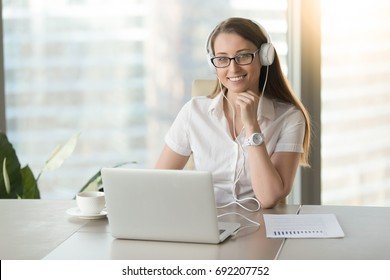 Smiling businesswoman wearing headphones with laptop posing at workplace, happy woman in headset looking at camera while enjoying listening corporate business course, online study, headshot portrait