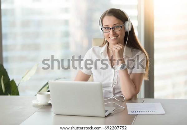 Улыбающаяся деловая женщина в наушниках с ноутбуком позирует на рабочем месте, счастливая женщина в гарнитуре смотрит на камеру во время прослушивания корпоративный бизнес-курс, онлайн-исследование, портрет